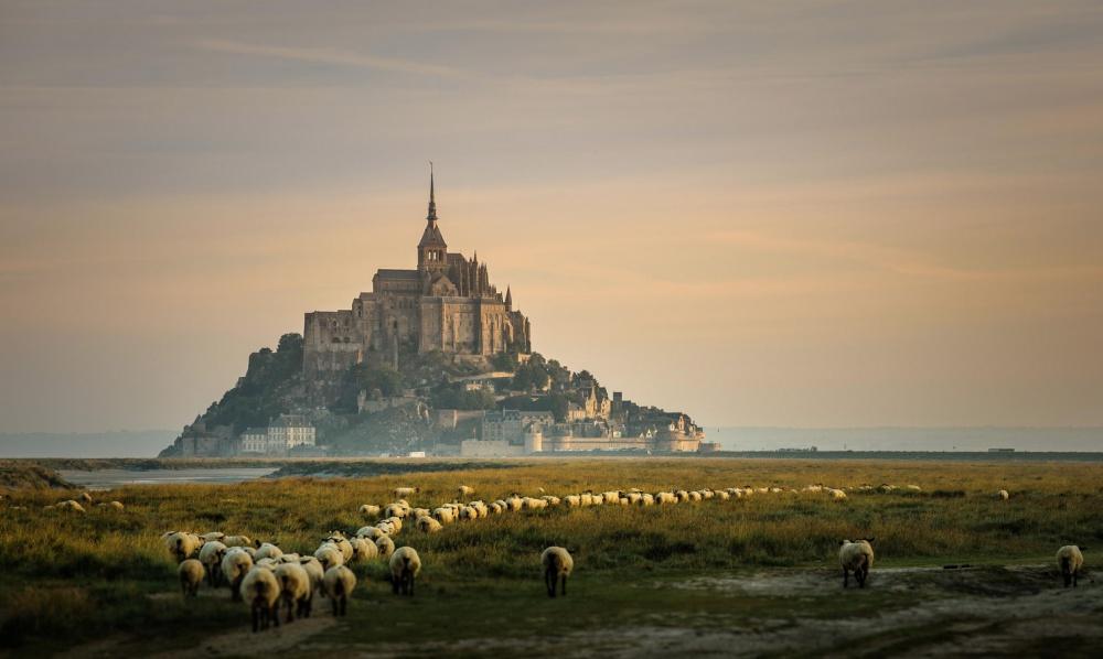Мон-Сен-Мишель, Франция Неприступный замок Мон-Сен-Мишель, со всех сторон окруженный морем, — одна из самых популярных достопримечательностей Франции после Парижа. Построенный в 709 году, он до сих пор выглядит
