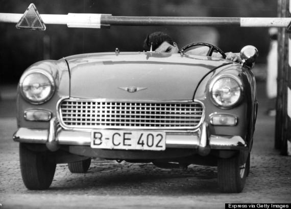 Австриец Хайнс Мийкснер, его невеста и будущая теща покидают ГДР в машине с откидным верхом и низкой посадкой - чтобы проехать под шлагбаумом пограничного КПП (Express/Archive Photos/Getty Images)