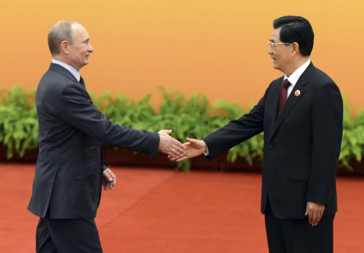 Chinese President Hu Jintao, right, shakes hands with Russian President Vladimir Putin at the Shanghai Cooperation Organization (SCO) summit in the Great Hall of the People in Beijing,  China Thursday, June 7, 2012.  (AP Photo/Mark Ralston, Pool)