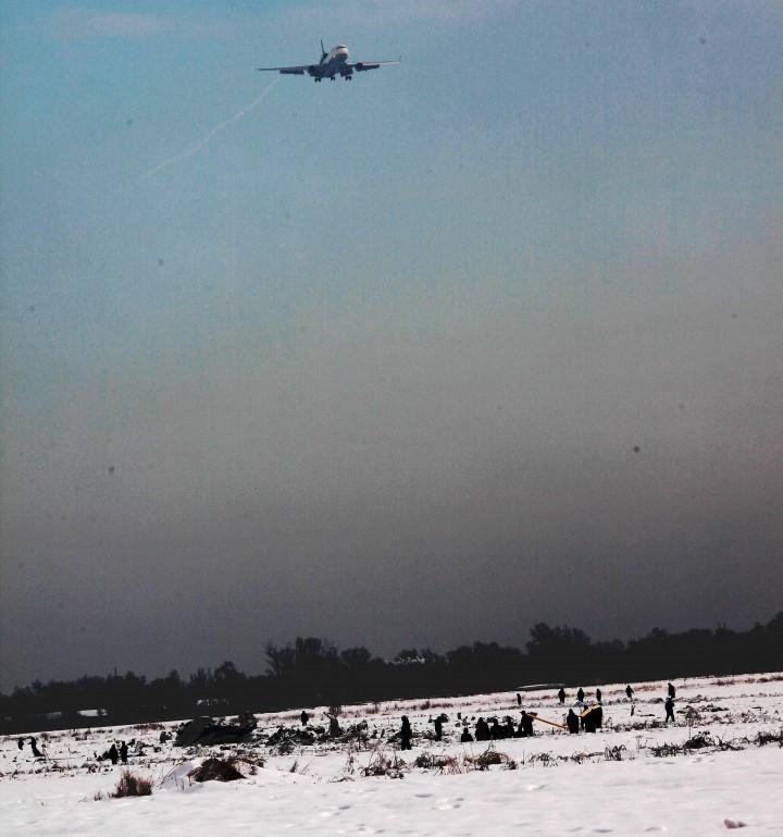 Другой борт готовится к посадке, а внизу люди разгребают последствия авиакатастрофы.