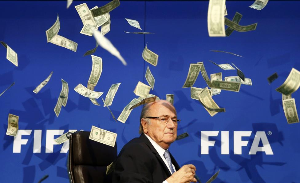 Banknotes are thrown at FIFA President Sepp Blatter as he arrives for a news conference after the Extraordinary FIFA Executive Committee Meeting at the FIFA headquarters in Zurich, Switzerland, July 20, 2015. REUTERS/Arnd Wiegmann