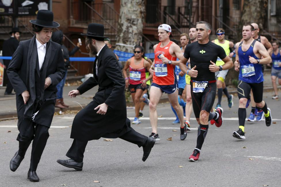 Orthodox Jewish men try to cross Bedford Avenue in the Williamsburg section of Brooklyn in front of former professional road racing cyclist Laurent Jalabert (runner in black ) of France, during the 2015 New York City Marathon, November 1, 2015. REUTERS/Shannon Stapleton