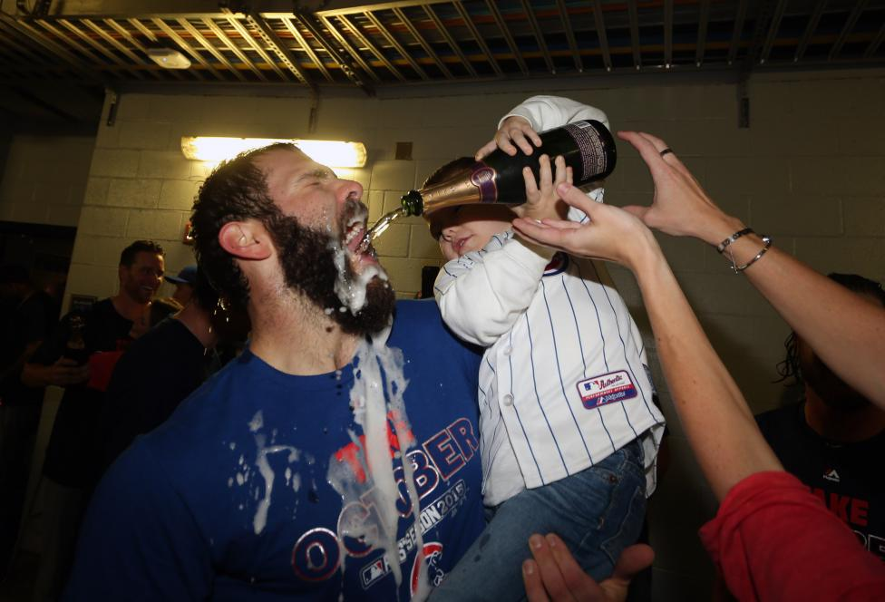 Chicago Cubs starting pitcher Jake Arrieta celebrates with his son Cooper after defeating the Pittsburgh Pirates in the National League Wild Card playoffs in Pittsburgh, October 7, 2015. Charles LeClaire-USA TODAY Sports