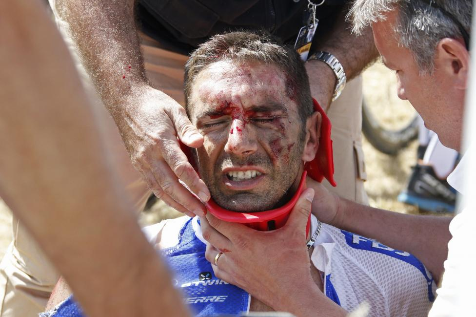 FDJ rider William Bonnet of France receives medical help as he sits on the ground after a fall during the 159,5 km (99 miles) third stage of the 102nd Tour de France cycling race from Anvers to Huy, Belgium, July 6, 2015. REUTERS/Eric Gaillard