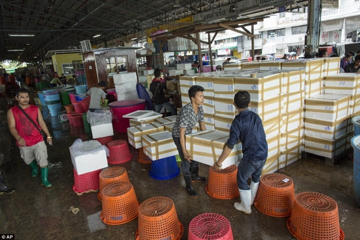 Рабочие переносят коробки с замороженными креветками на рынке морепродуктов в Махачае.
