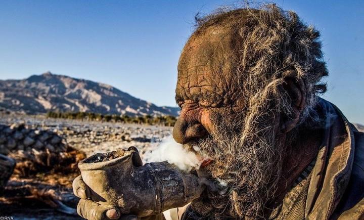 Мужчина, который не моется уже более 60 лет, курит навоз с помощью трубки.