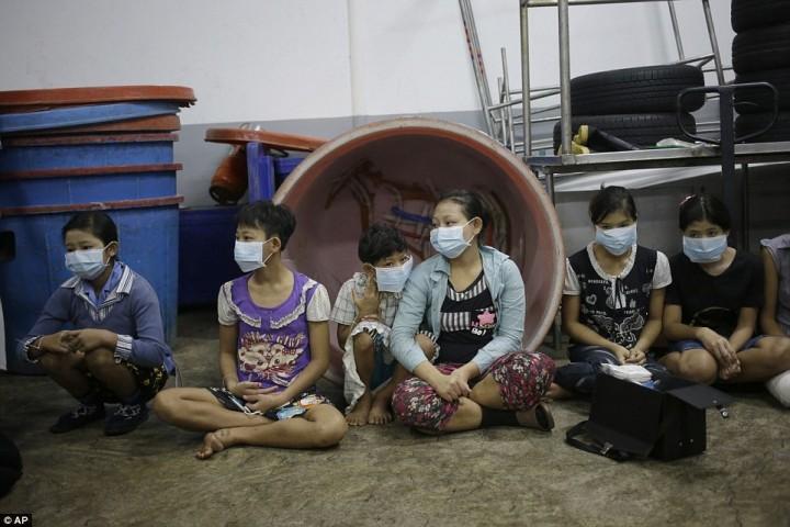 Несовершеннолетние работники и работницы ждут, когда их зарегистрируют уполномоченные лица, во время рейда на фабрику по чистке креветок в провинции Самутсакхон. Жители беднейших стран мира, например, Мьянмы, приезжают в провинцию Самутсакхон, чтобы получить работу на предприятиях по чистке морепродуктов, и попадают в трудовое рабство.