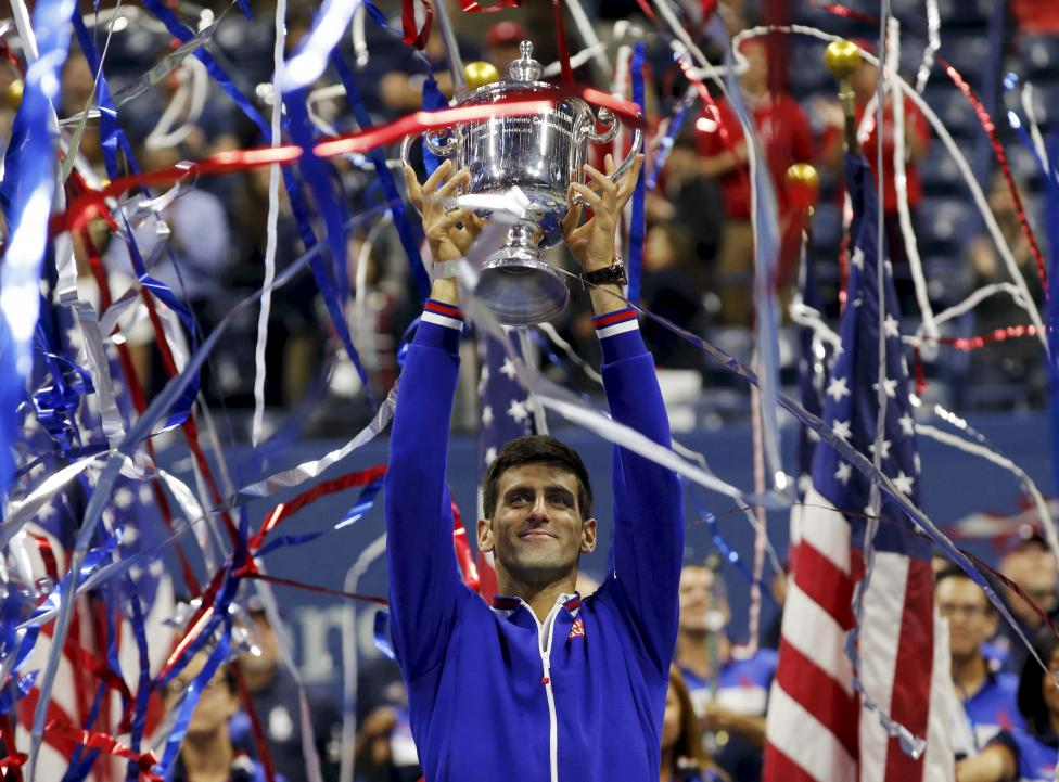 Novak Djokovic of Serbia holds up the U.S. Open trophy after defeating Roger Federer of Switzerland in their men's singles final match at the U.S. Open Championships tennis tournament in New York, September 13, 2015. REUTERS/Mike Segar