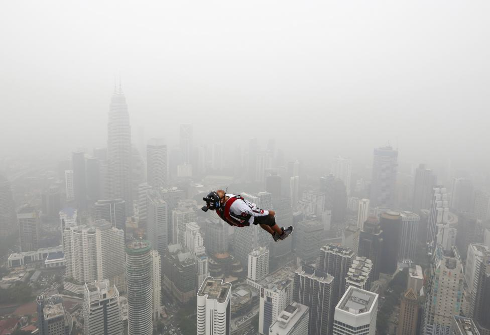 A BASE jumper leaps from the 300-metre high Kuala Lumpur Tower during the International Tower Jump in which more than 100 people take part, on a hazy day in Kuala Lumpur, Malaysia, October 2, 2015. REUTERS/Olivia Harris