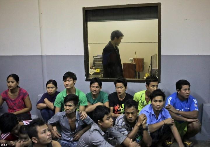 Рабочие из Мьянмы сидят на полу, пока работники Департамента специальных расследований Таиланда обыскивают помещение фабрики по чистке креветок во время рейда в провинции Самутсакхон.