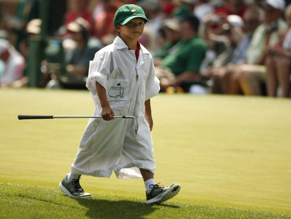 Tiger Woods' son Charlie carries one of his father's clubs along the fourth hole during the par 3 event held ahead of the 2015 Masters at Augusta National Golf Course in Augusta, April 8, 2015. REUTERS/Phil Noble