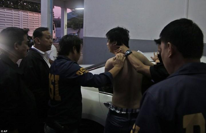 Работники Департамента специальных расследований Таиланда задерживают мужчину, который пытался сбежать во время рейда.
