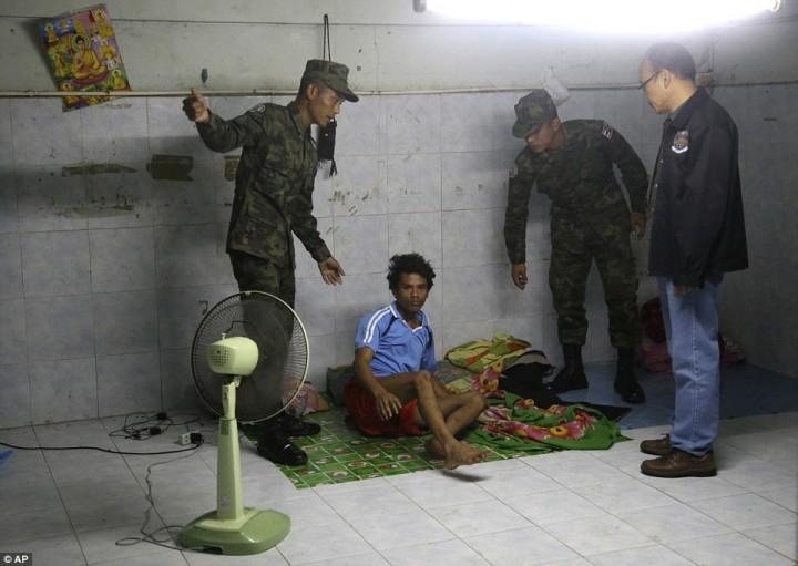 Тайские солдаты и работник Департамента специальных расследований Таиланда будят рабочего во время рейда на фабрику по чистке креветок.