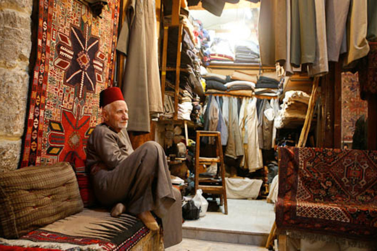 A man sits in a market in Aleppo city in Syria March 15, 2007. Aleppo, Syria's second city and one of the oldest inhabited in the world, is enjoying a renaissance that is restoring the ancient trading hub whose magnificent buildings rivalled Istanbul's in Ottoman times. Picture taken March 15, 2007. To match feature SYRIA-CITY/ REUTERS/ Khaled al-Hariri (SYRIA)