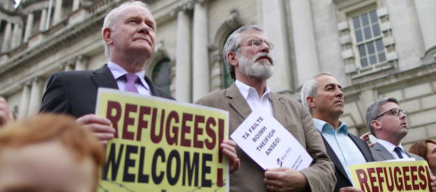 Sinn Fein's Martin McGuinness, left, and Gerry Adams join members of the public for a vigil in support of the refugees crisis abroad as some hundreds of people gathered at Belfast city hall, Northern Ireland, Monday, Sept. 7, 2015. Vigils were held across many city's in Ireland for the 'Humanitarian tragedy', following Belfast's vigil a special meeting of the council, was held. (AP Photo/Peter Morrison)