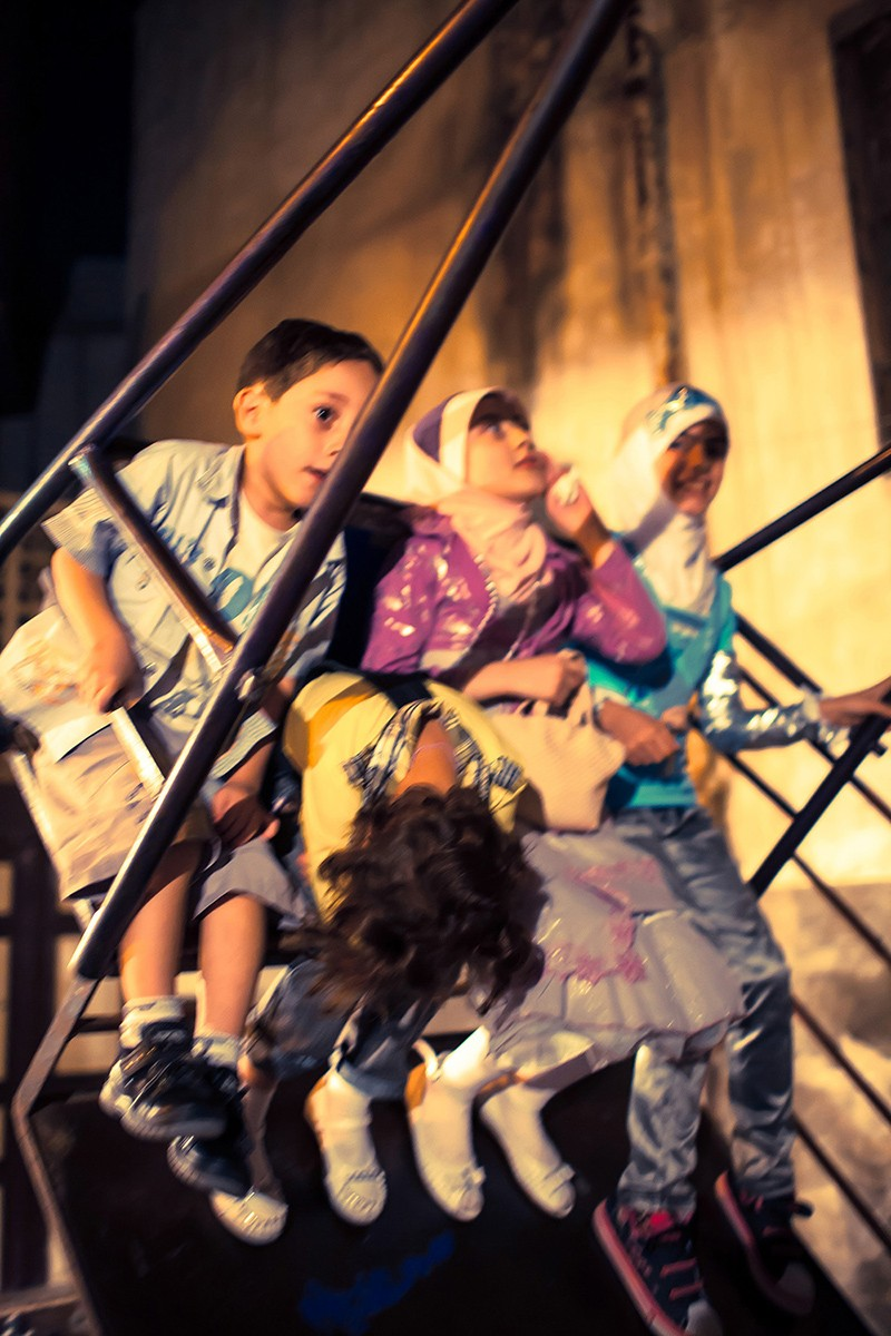 """Children enjoying a swing in Central Damascus. FOR GALLERY FOR PHOTOGRAPHY PAGE.- TO GO LIVE EARLY SEPTEMBER,.... FOR GALLERY/SLIDESHOW FOR PHOTOGRAPHY PAGE – CAN BE PRODUCED ANY TIME BUT SHOULD GO LIVE IN EARLY SEPTEMBER... AN IMPERFECT NORMALITY An Imperfect Normality is a retrospective exhibition of pictures by Tommie Lehane of a Syria that was. Like dozens, and more, periods throughout Syria's long history, this time is now past and consigned to the history books. Currently ravaged by war and chaos, it is hard to imagine a place that, to those who lived within its territory or who crossed its borders, was a relatively normal place to be. This work seeks to document a normality whilst hinting at its imperfections and considering the effect of war as a method of change. The Images are from 2005 and 2009 when the photographer visited initially as a tourist and on the second occasion stayed mainly in the house of a friend in a tiny village. He was there for a few weeks for each period of shooting. Al Hamidiyah village The work is focused around the normality of life in a place where the obvious undercurrents have now resulted in the awful situation that now exists. Lehane had planned to return in 2012 to focus on the """"Greeks of Al Hamidiyah"""", the village where some of these images were taken, but events overtook his plans and through war the Syria he had come to know no longer exists. Lehane's practise is primarily centered on the exploration of place. Unusually, he has a dual focus on the Middle East and a small village Castlegregory, in the Dingle Penninsula. Tommie has been widely exhibited in Ireland and Europe and also at the start of 2015 in war torn Aleppo in Syria. In 2014 Tommie Lehane was the recipient of the Alliance Française Photography Laureate. The exhibition runs in the Fire House Gallery Dublin from September 10th to September 25th."""