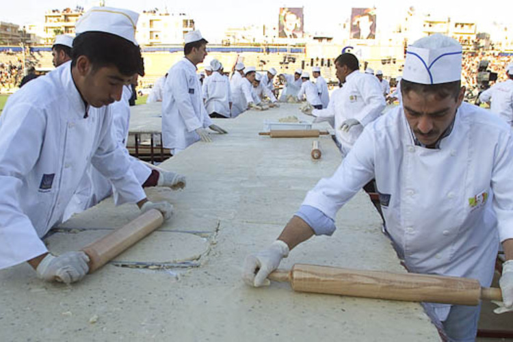 Syrian chefs prepare a giant four-tonne pistachio marzipan cake at a stadium in Aleppo. July 1, 2003. Syria won its first entry in the Guinness Book of Records with the 200-square-metre (2,150 square foot) cake, beating a Dutch record. REUTERS/Khaled al-Hariri IE/GB