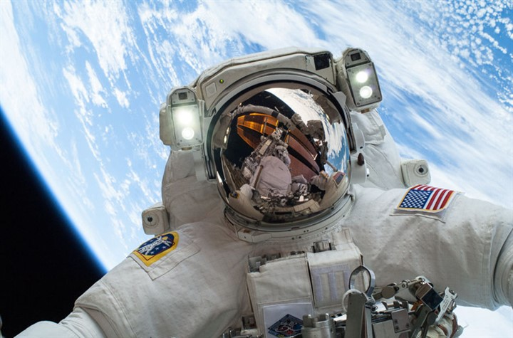 """This NASA photo shows on December 24, 2013, as NASA astronaut Mike Hopkins, Expedition 38 Flight Engineer, participates in the second of two spacewalks, spread over a four-day period, which were designed to allow the crew to change out a degraded pump module on the exterior of the Earth-orbiting International Space Station. He was joined on both spacewalks by NASA astronaut Rick Mastracchio, whose image shows up in Hopkins' helmet visor. The pump module controls the flow of ammonia through cooling loops and radiators outside the space station, and, combined with water-based cooling loops inside the station, removes excess heat into the vacuum of space. AFP PHOTO/NASA = RESTRICTED TO EDITORIAL USE - MANDATORY CREDIT """"AFP PHOTO / NASA/ HANDOUT"""" - NO MARKETING NO ADVERTISING CAMPAIGNS - DISTRIBUTED AS A SERVICE TO CLIENTS ="""