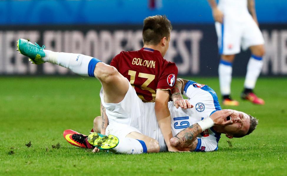 Slovakia's Juraj Kucka is fouled by Russia's Aleksandr Golovin. REUTERS/Christian HartmannLivepic