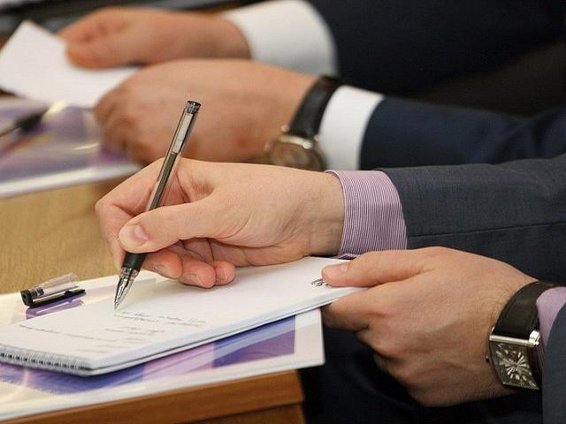 человек в костюме пишет на бумаге ручкой