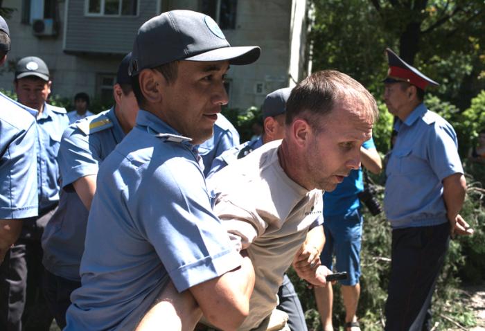 милиционер уводит активиста во время протестов против вырубки деревьев в бишкеке