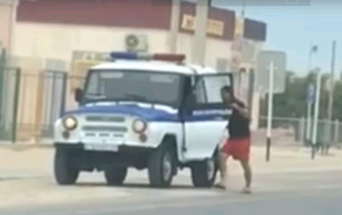 актау полицейский в шортах садится в патрульное авто