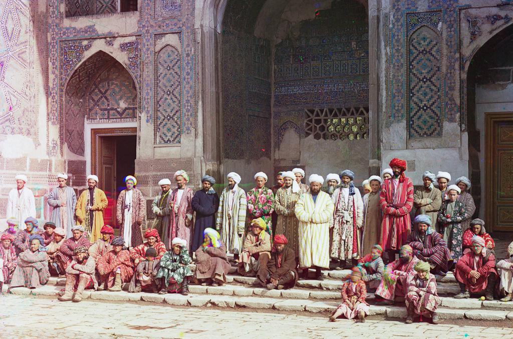 Мужчины и мальчики на ступенях медресе Шердор на площади Регистан в Самарканде